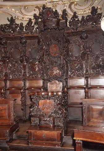 La cattedra vescovile in legno di noce con inta...
