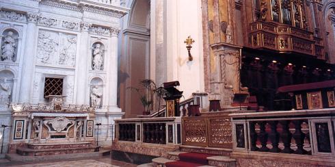 Scorcio del presbiterio sistemato nel 2000:altare e amboni lignei, al centro e a sinistra delal tribuna, realizzati da maestranze di Ortisei