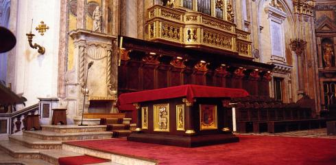L'altare ligneo ornato da formelle in bronzo dorato e la cattedra episcopale.