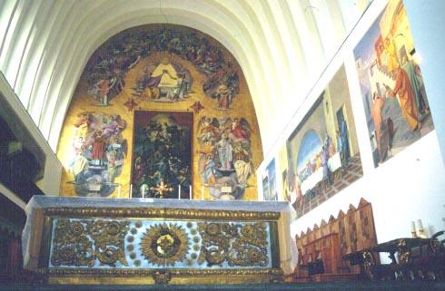 Altare con paliotto ligneo barocco nella cattedrale ricostruita nel 1958. Sullo sfondo e sulla parete laterale destra l'apparato iconografico realizzato negli anni Sessanta.